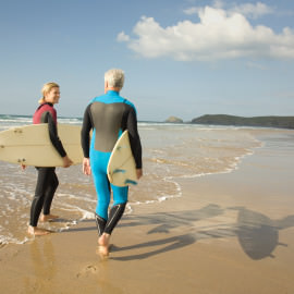 Mature couple with surfboards