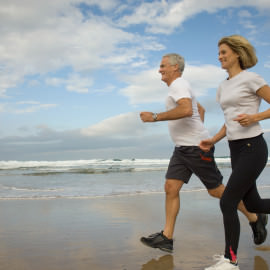 Mature Couple Jogging on Beach